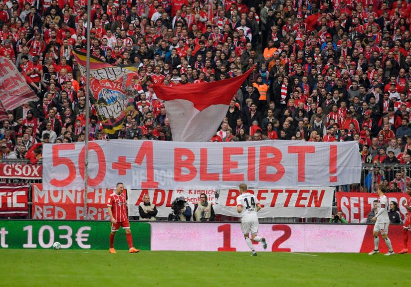 Image showing bayern fans holding banners of '50 + 1' rule.